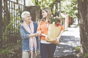 Smiling granddaughter is helping her grandmother to carry home the packages after shopping